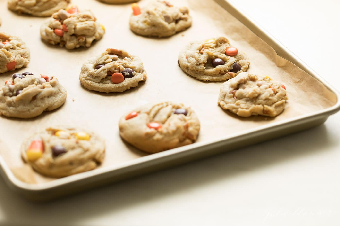 A gold sheet pan with monster cookies, candy corn and reese's candies peaking through.