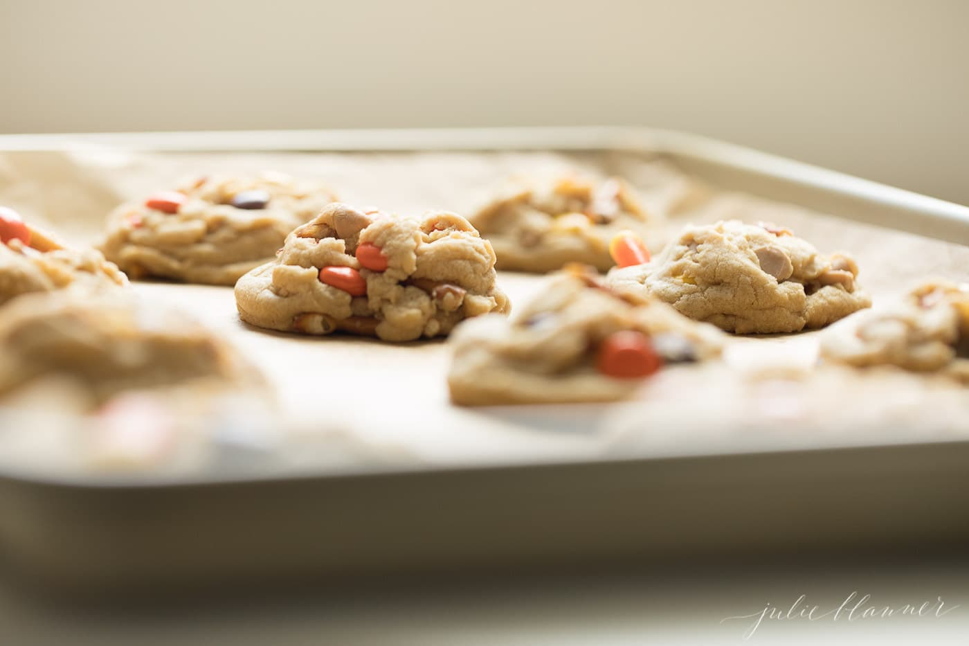 monster cookies on a gold sheet pan with parchment paper.
