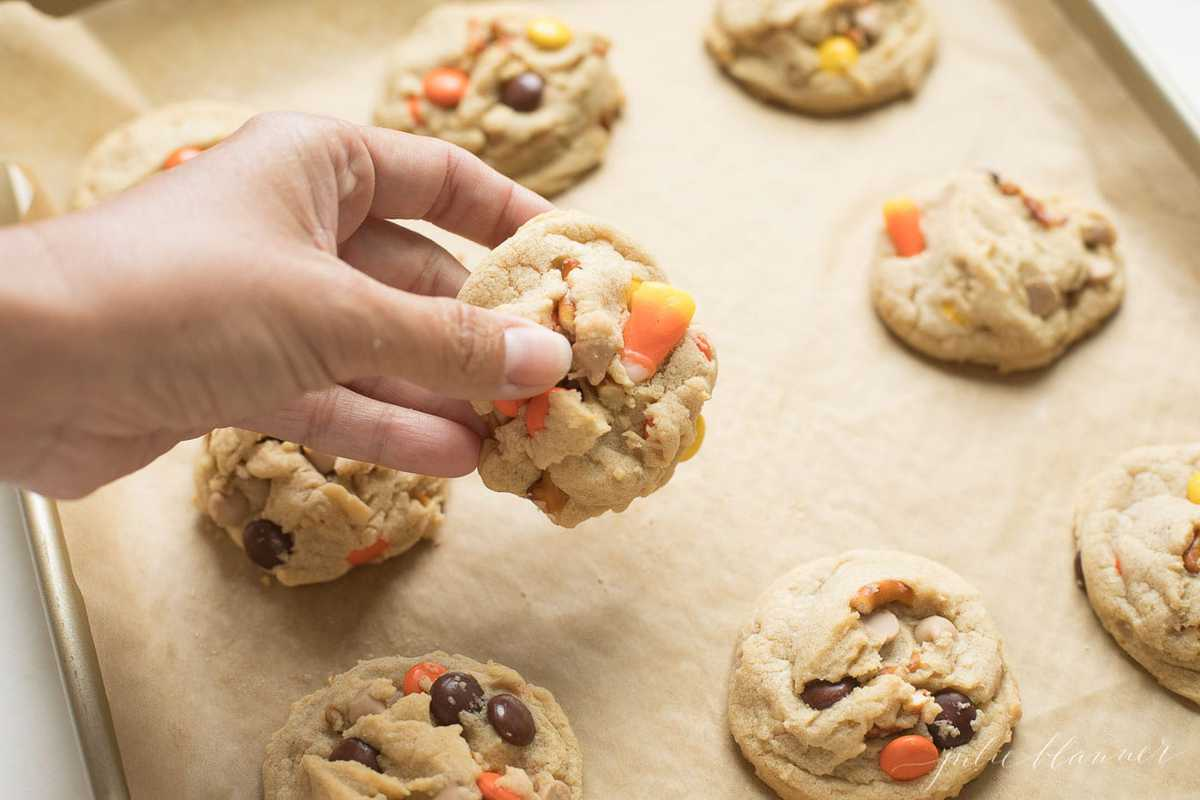 Monster Cookies on a baking sheet with a hand holding one cookie.