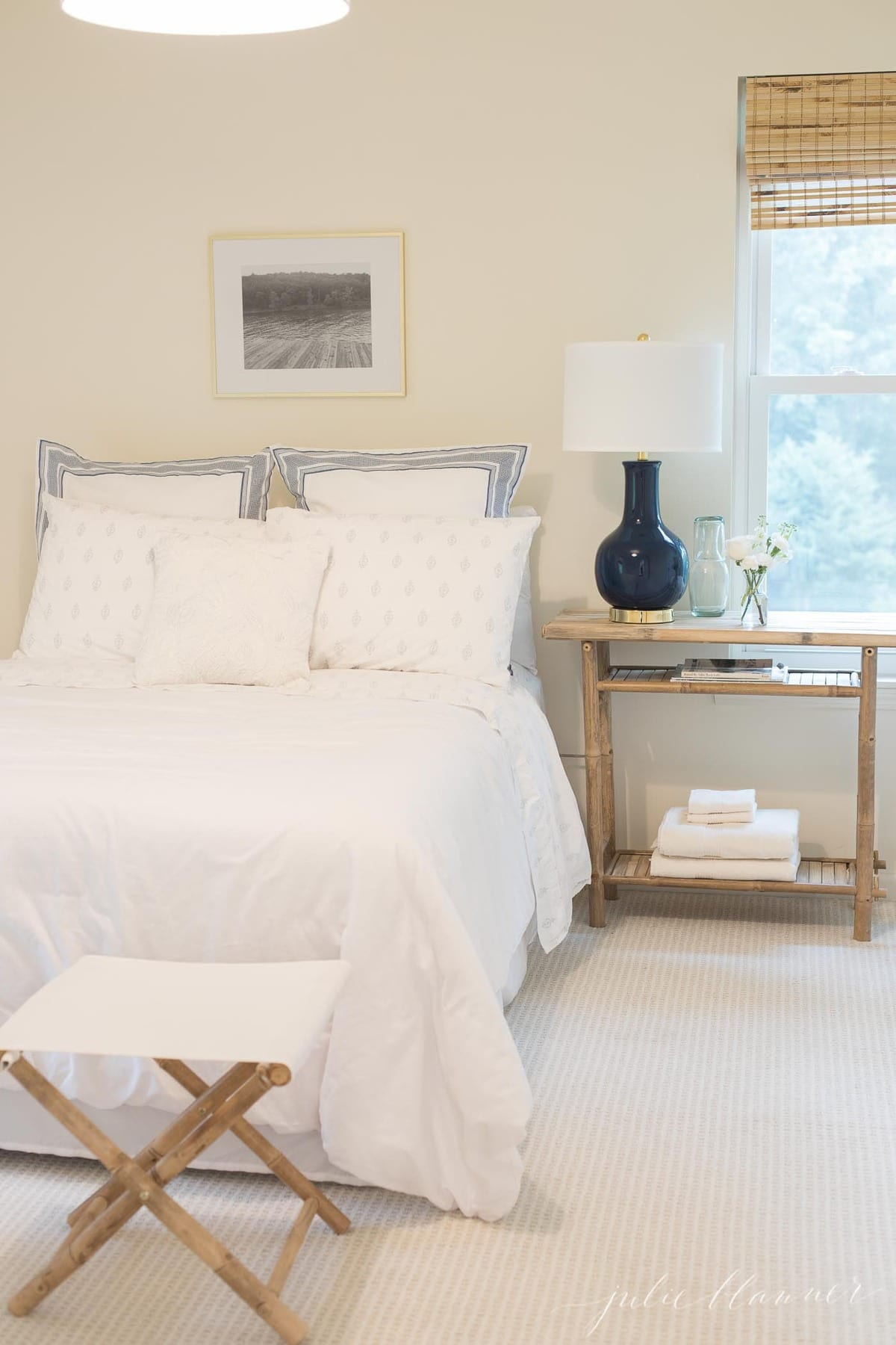patterned carpet in lake house bedroom decorated with white and blue and bamboo furniture