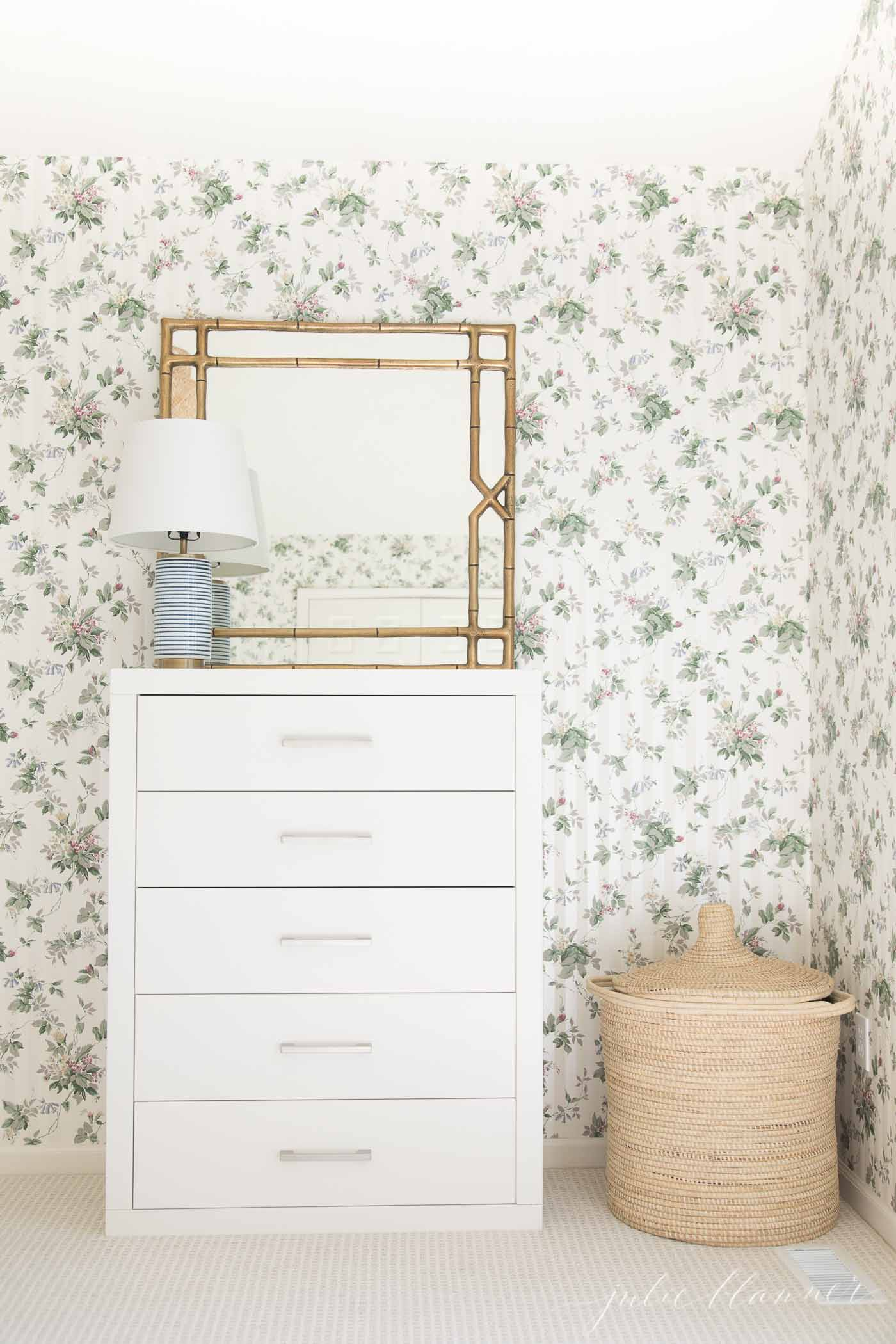 A white dresser in a bedroom with floral wallpaper and beige patterned carpet.