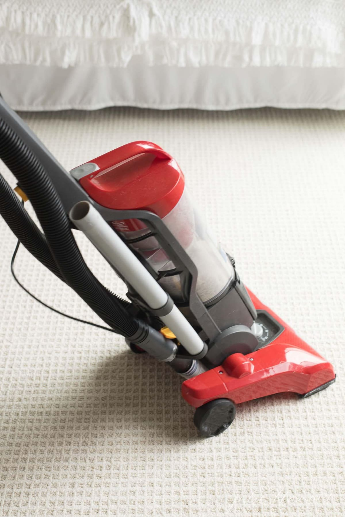 patterned carpet in a bedroom, red vacuum in motion.