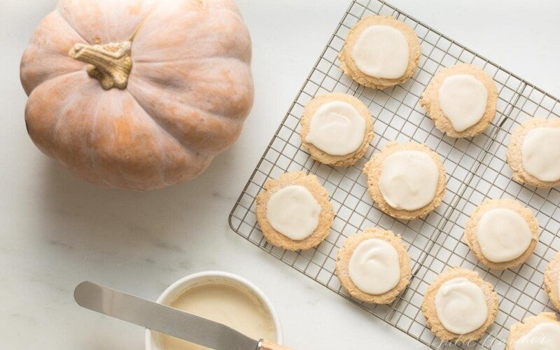pumpkin sugar cookies with cream cheese glaze on a cooling rack