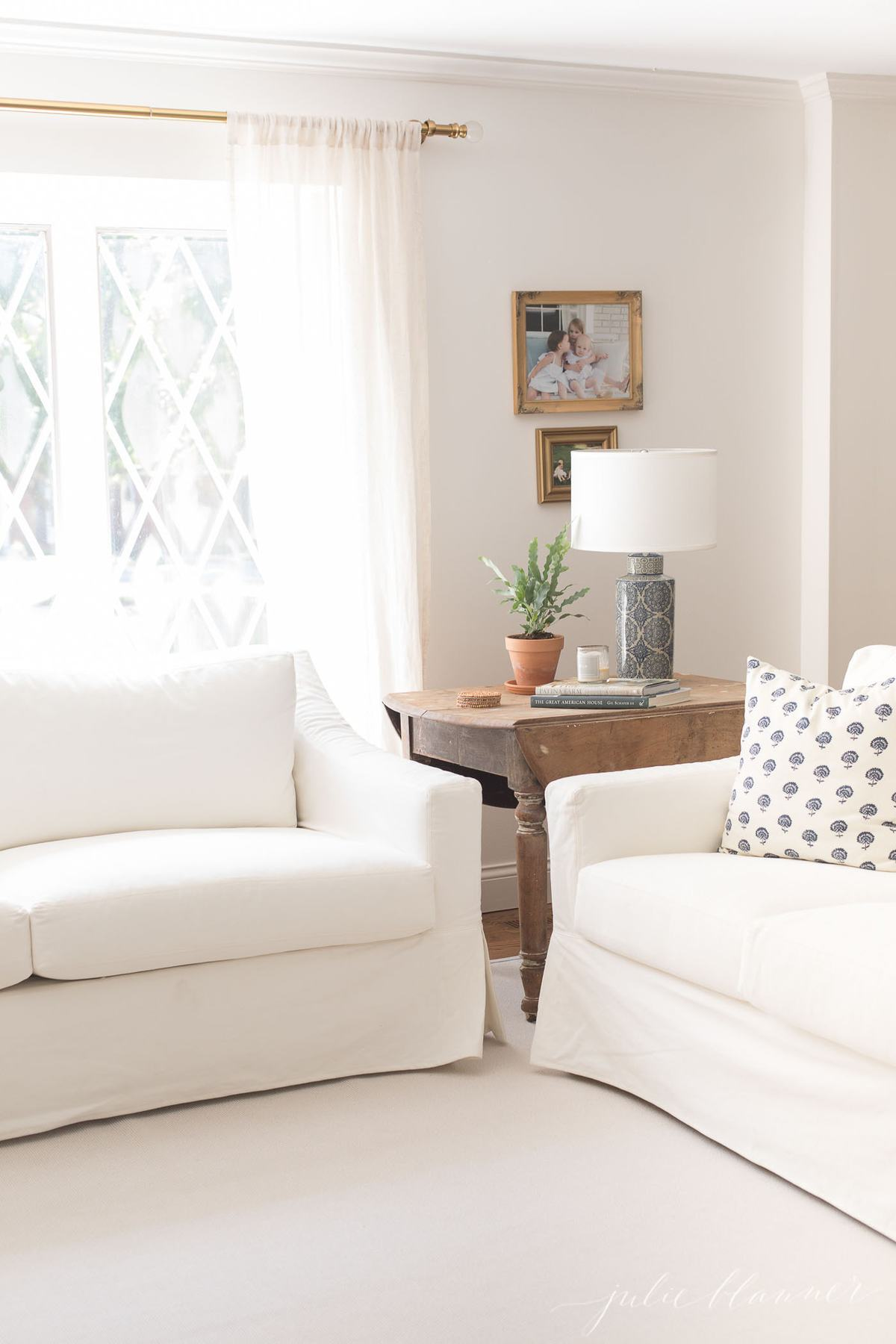 Two white sofas in a living room with a custom sisal rug with border on the floor.