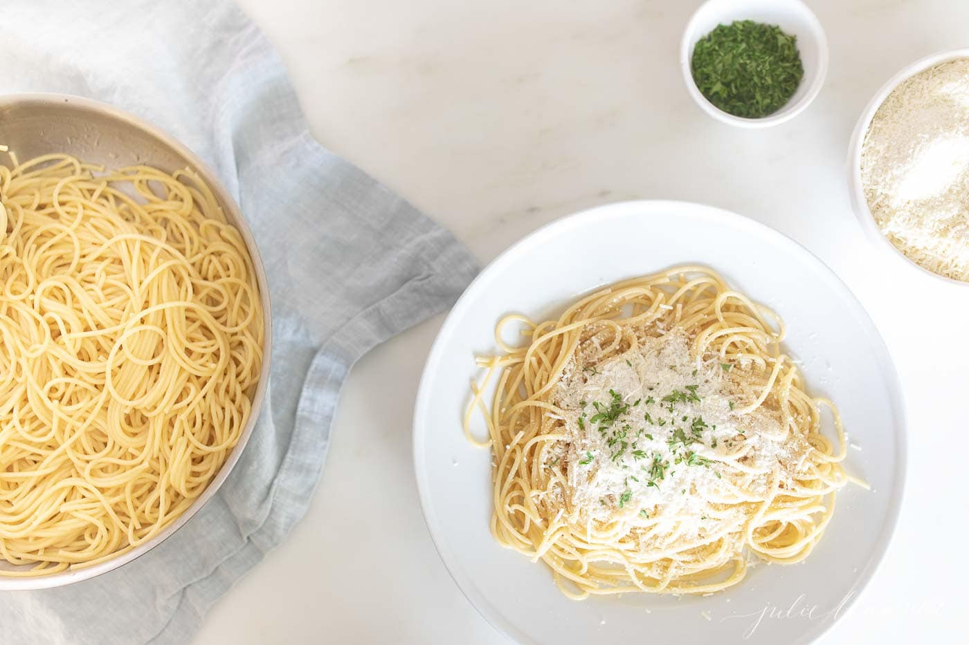 spaghetti on a plate sprinkled with mizithra cheese