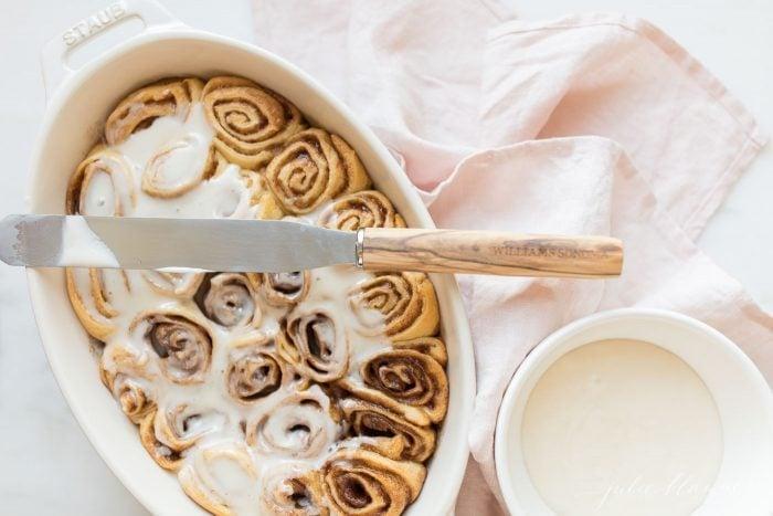 icing cinnamon rolls in baking dish