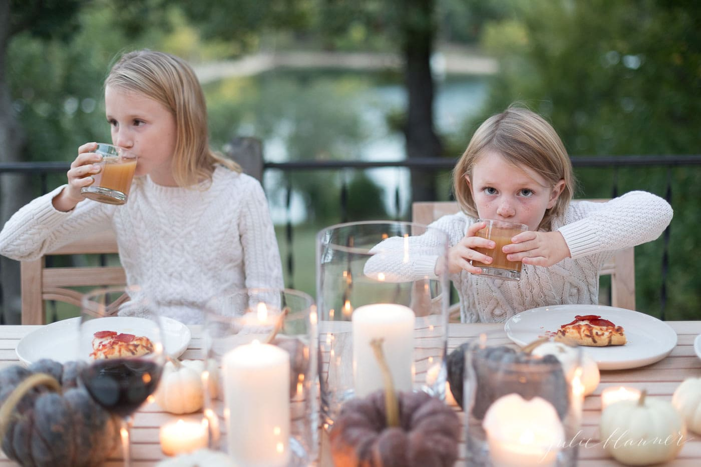 kids eating pizza and drinking apple cider at an outdoor dining table