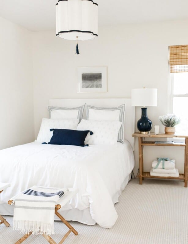 A guest bedroom with a stack of towels on the bedside table.
