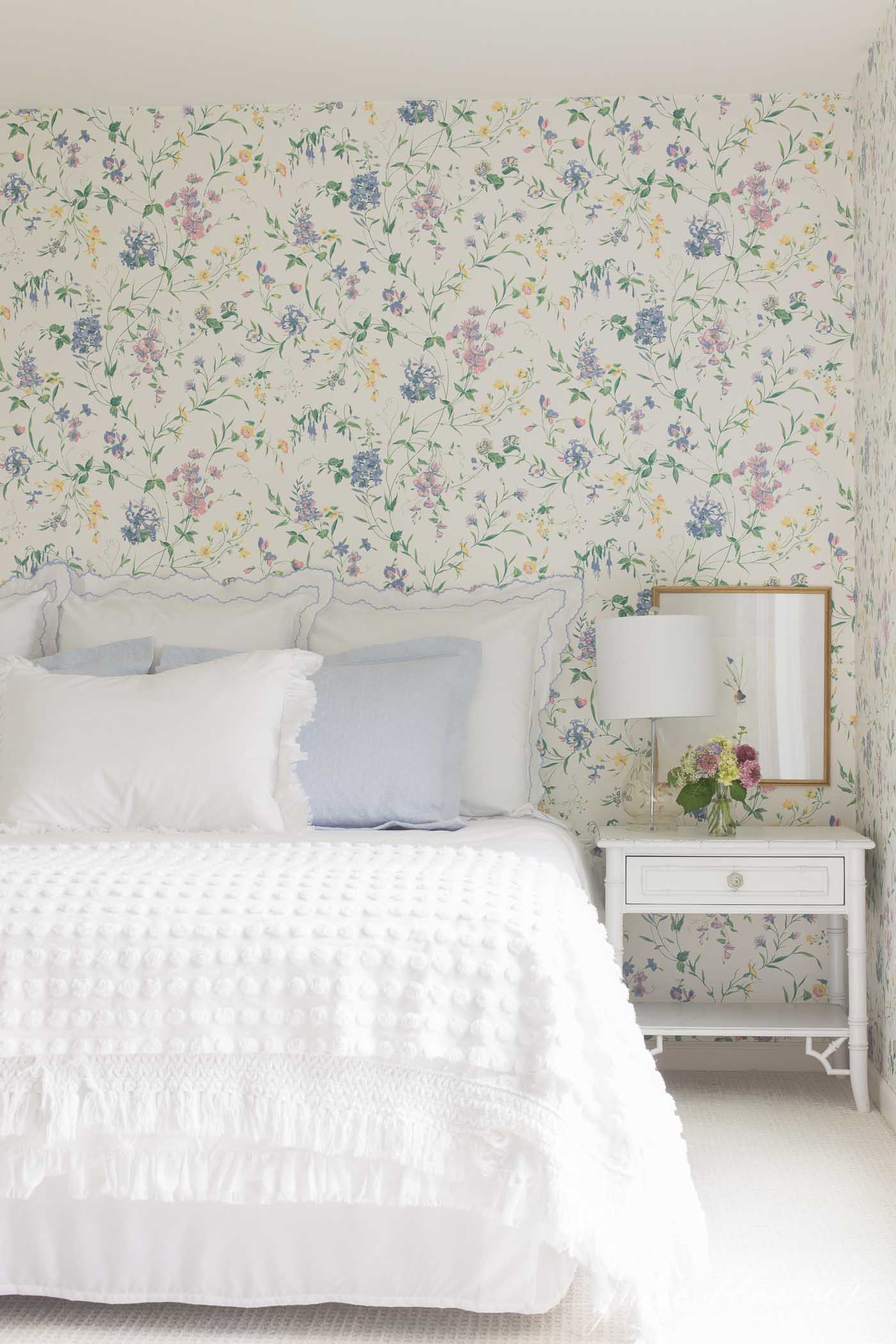 A floral wallpapered guest bedroom with blue and white bedding.