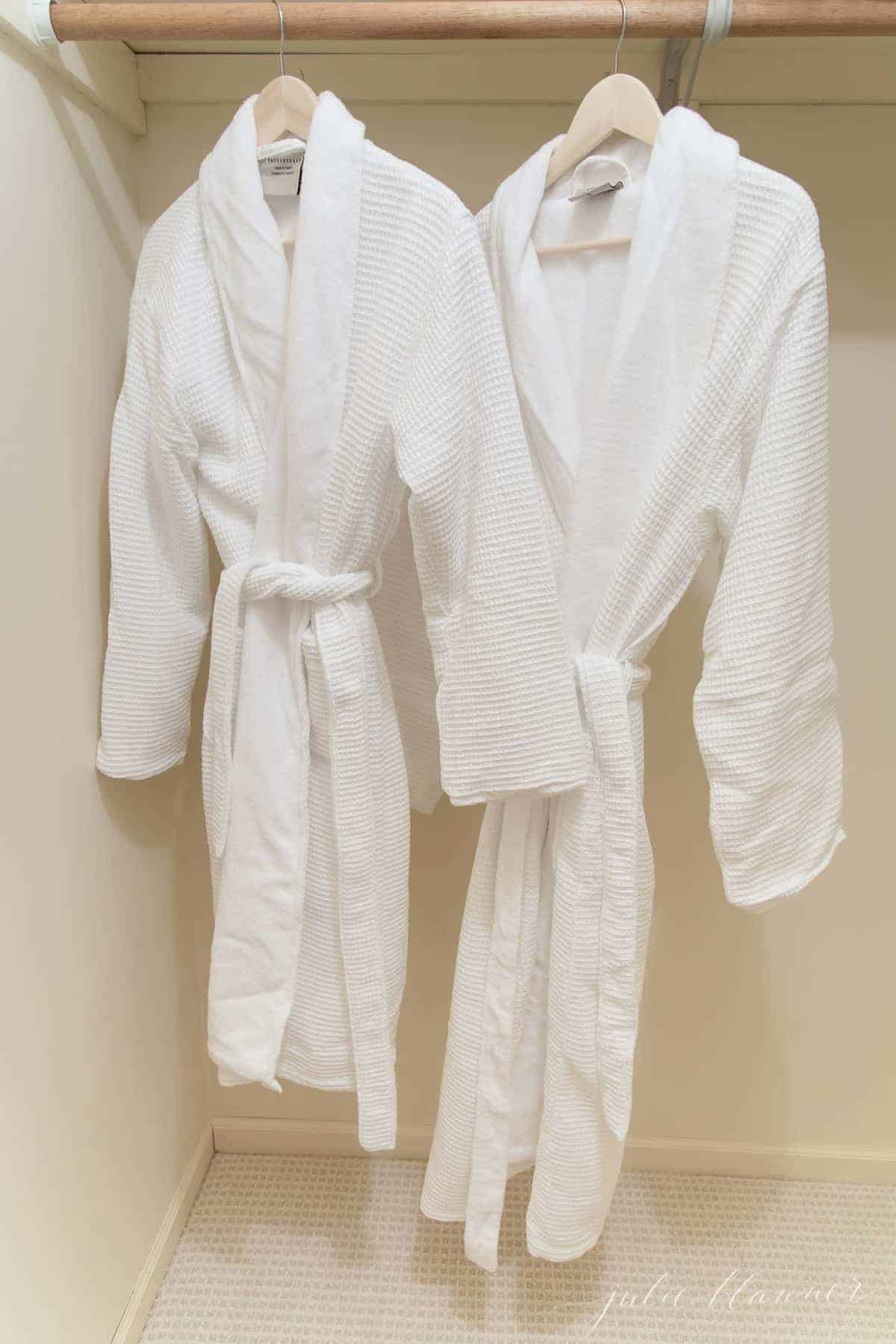 Two white bath robes hanging in a guest room closet.