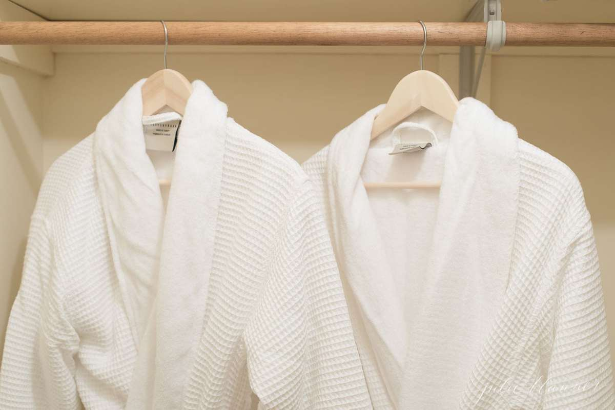 white robes hanging in a closet with more guest room ideas.