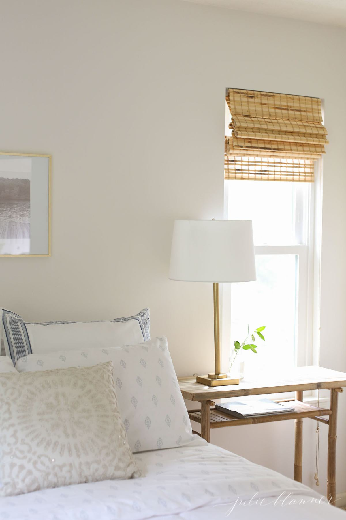 neutral guest room with blue and white bedding and natural furniture and window shades.