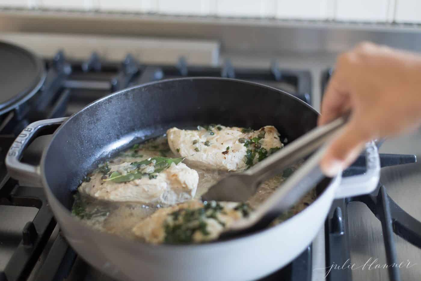 Chicken in white wine sauce in a gray saute pan, hand reaching in with tongs.