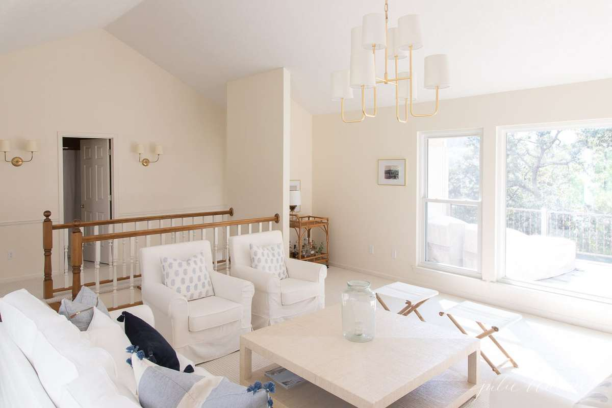 White furniture with blue pillows and a grass cloth style coffee table in a modern coastal living room.