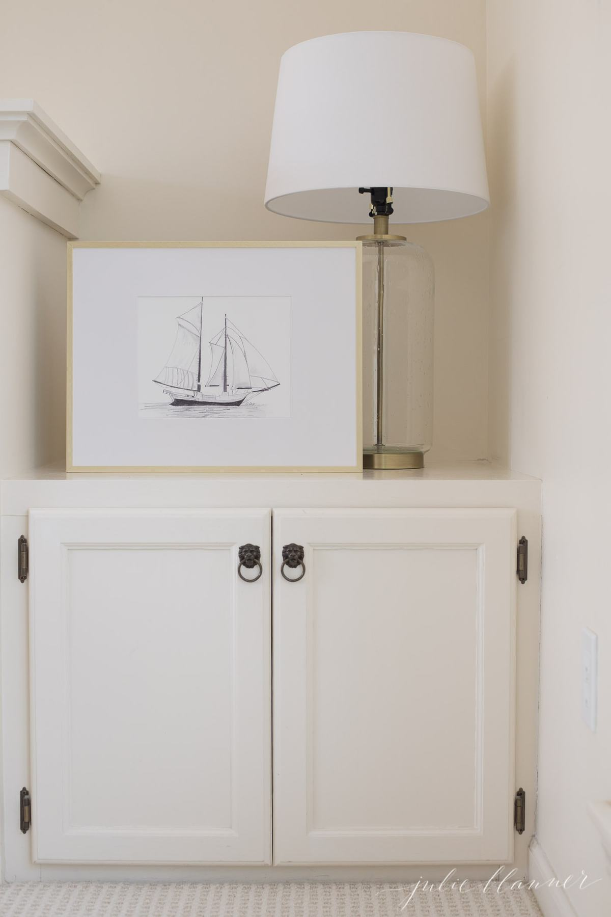 A gold framed boat picture on built in cabinets near a fireplace.