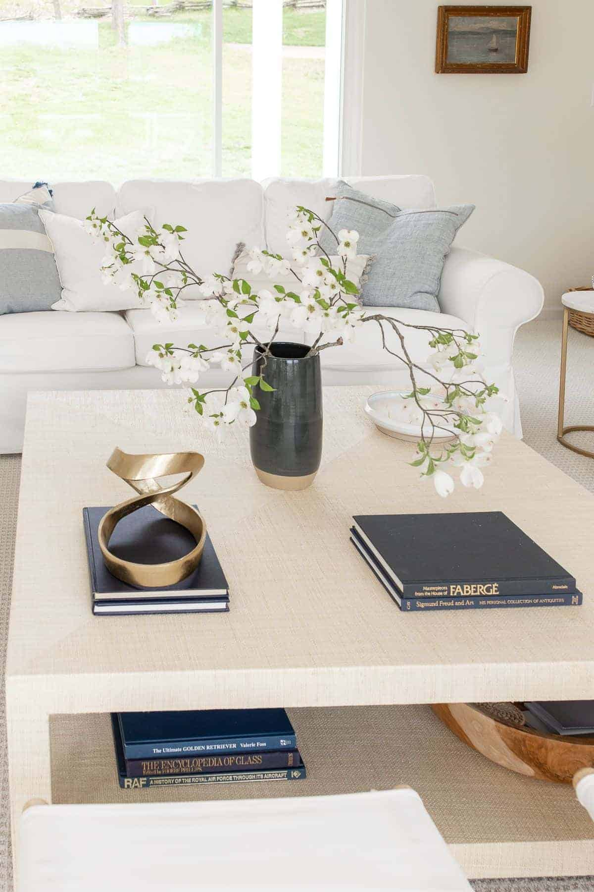 A raffia coffee table decorated in a coastal modern living room style, with a navy vase of blooming branches.