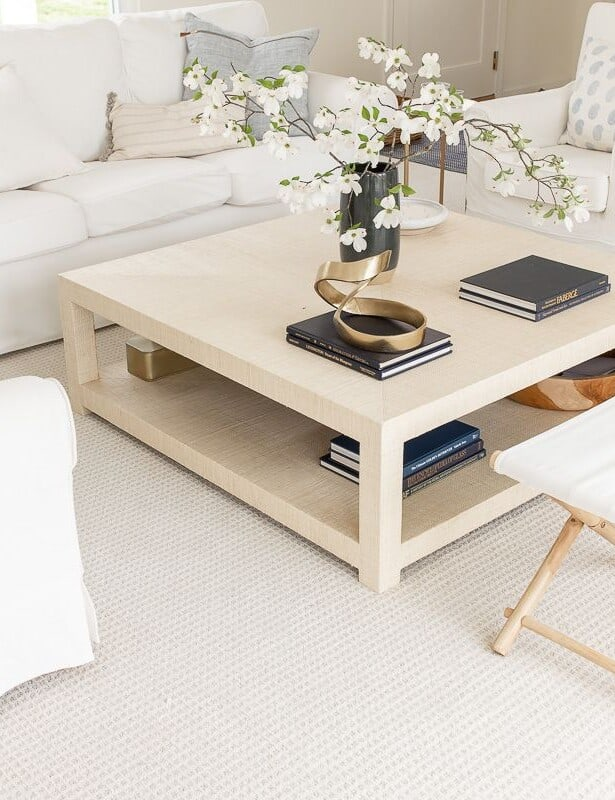 A white living room with white furniture and a raffia coffee table.