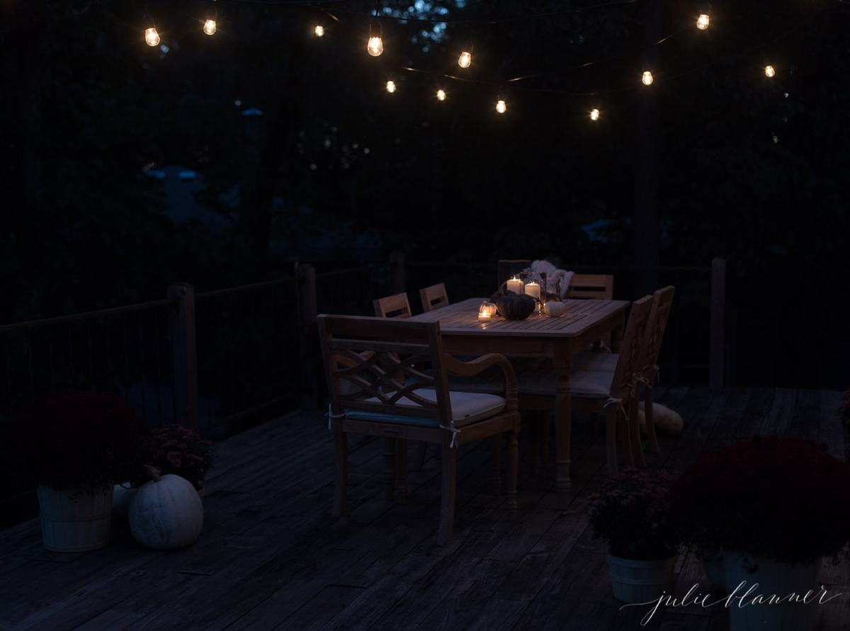 bulb lights over a table with pizza under the stars
