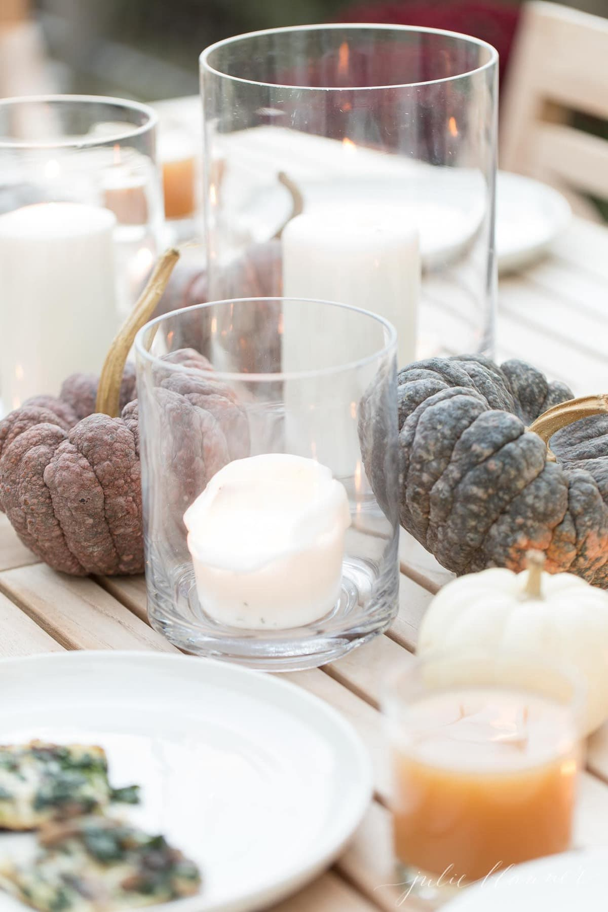 A centerpiece of glass hurricanes with candles and heirloom pumpkins on a wood table.