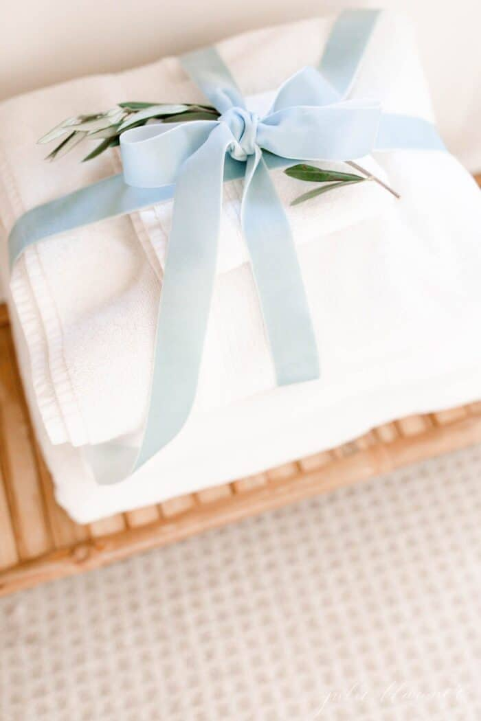 A stack of towels wrapped with velvet ribbon as a guest room idea at Christmas time.