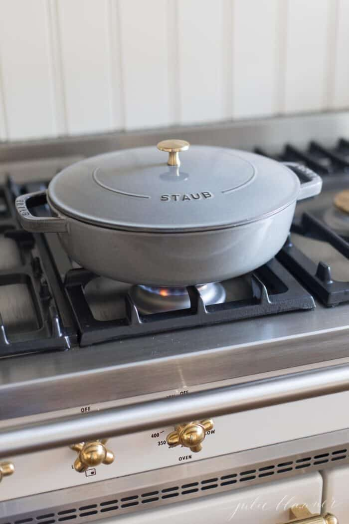 A gray cast iron saute pan with lid on a french range.
