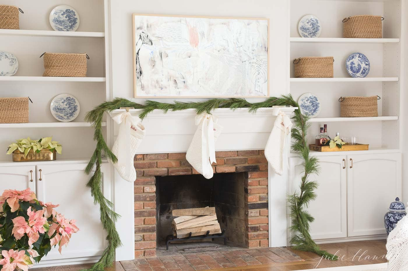 fresh pine garland on a fireplace mantel in a white living room.