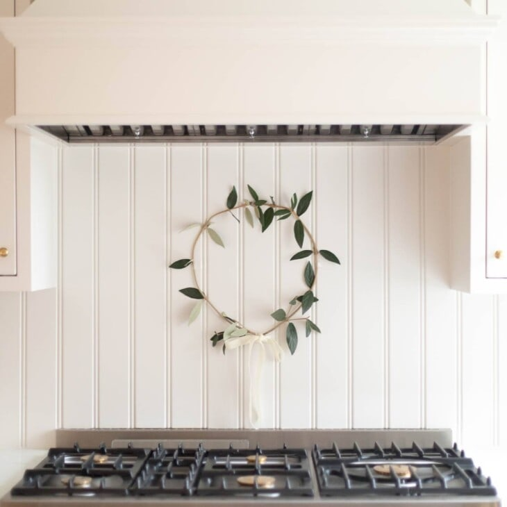 A cream kitchen with a simple greenery wreath hanging behind the range.