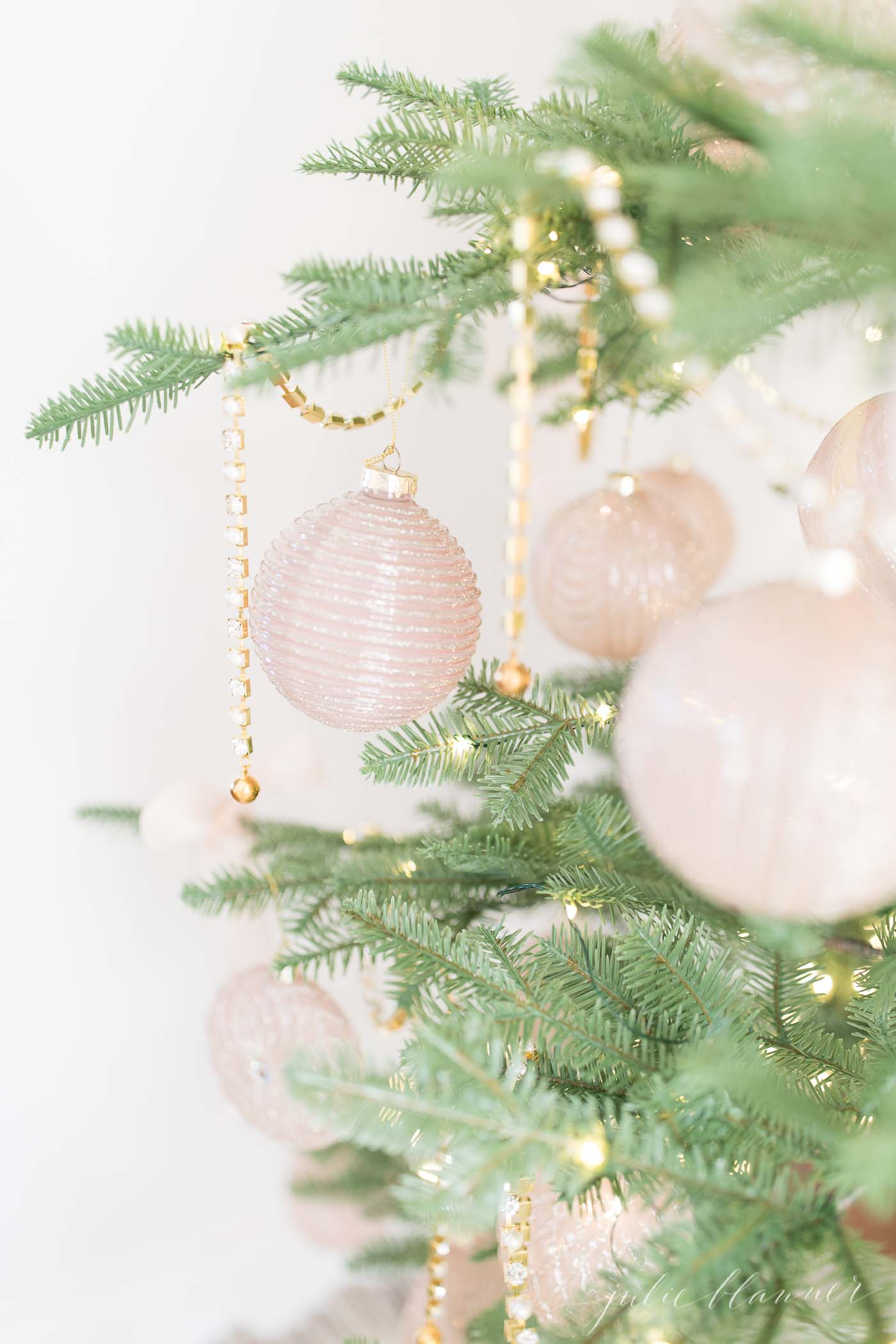 sparse christmas tree decorated in gold and pink ornaments