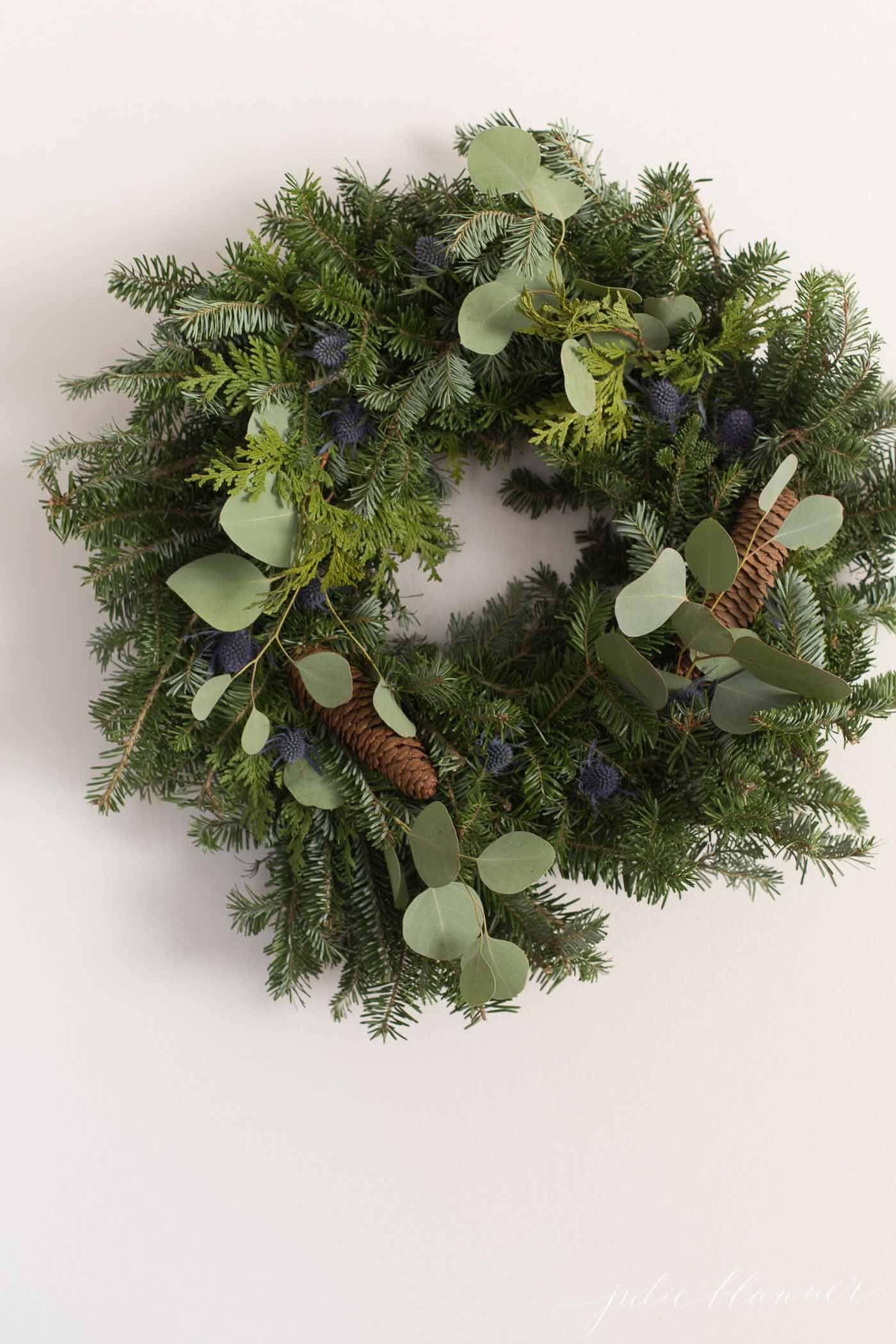 Fresh evergreen christmas wreath on a white wall.