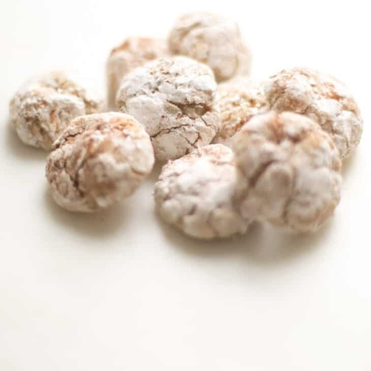 pile of eggnog cookies dusted in powdered sugar and spices on white surface