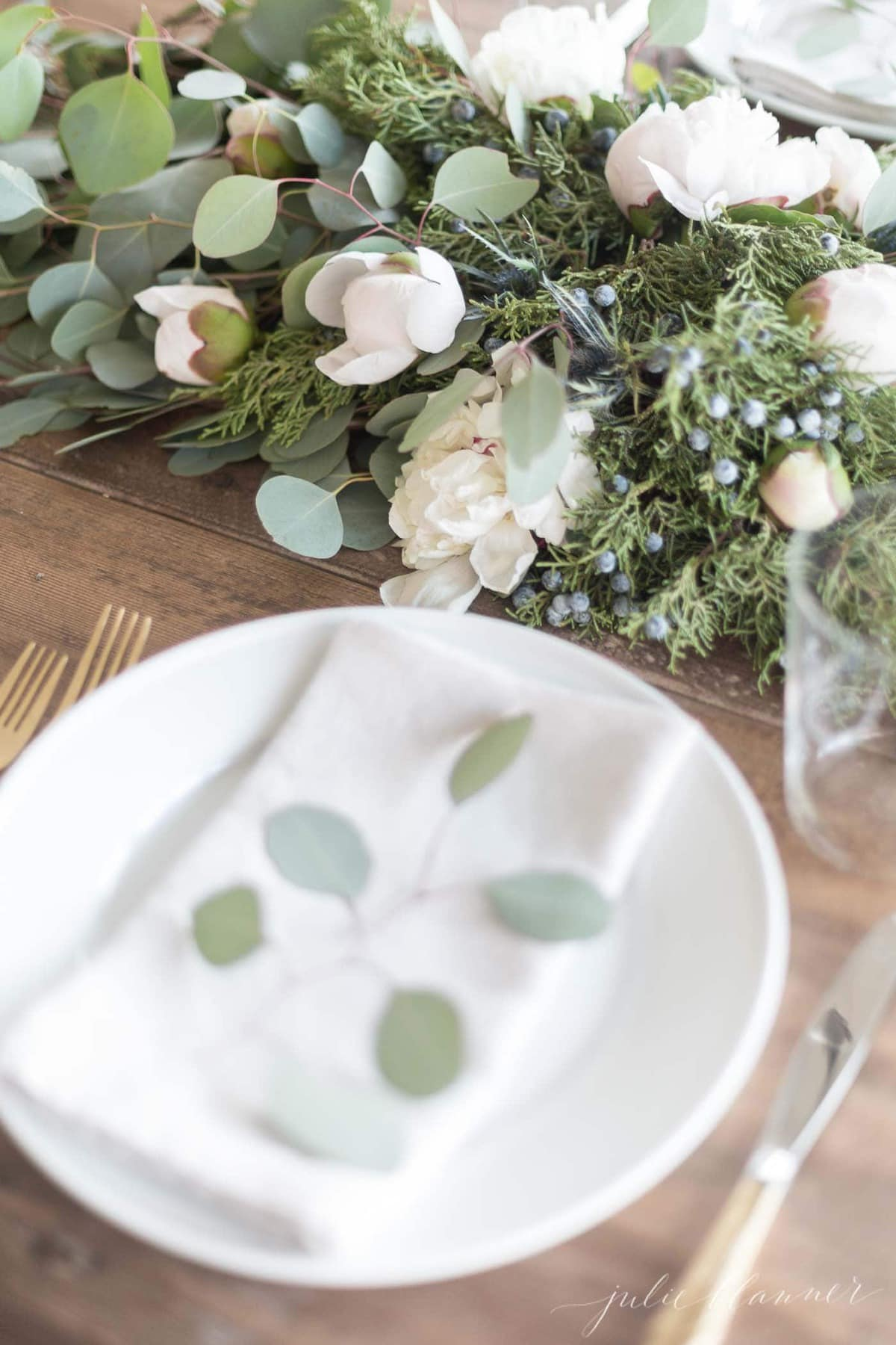 Christmas greens and fresh blooms on a dining room table.