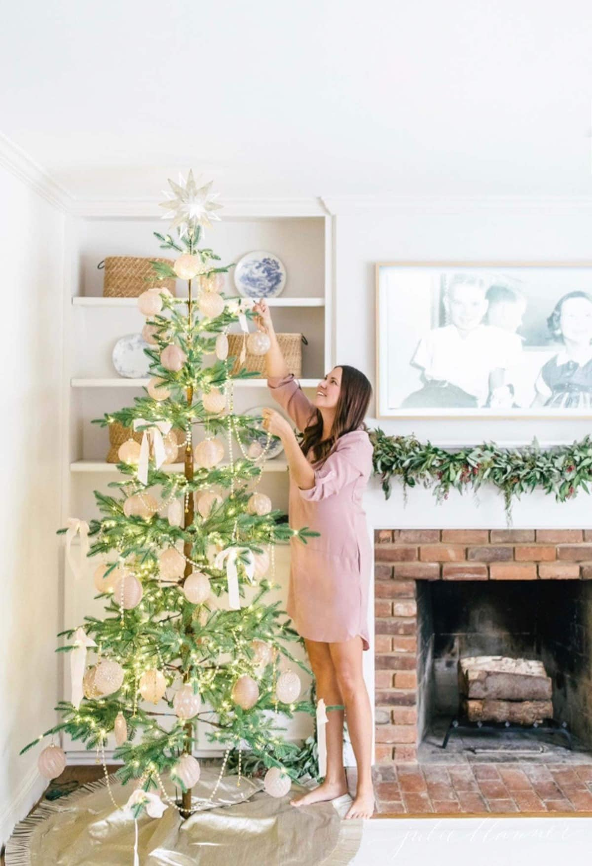 lifestyle blogger julie blanner decorating a sparse christmas tree in her living room