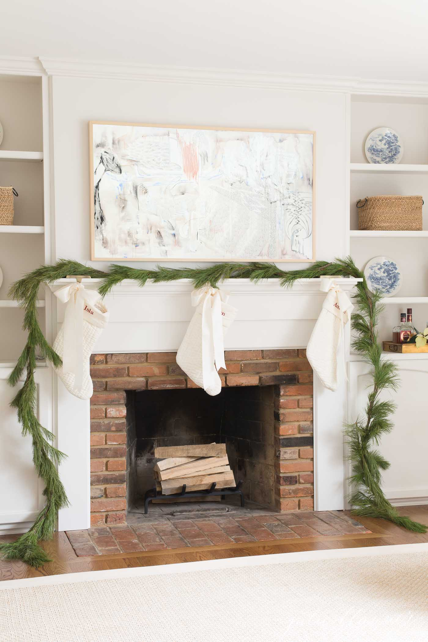 A living room fireplace with a fresh greenery garland and a Frame Tv hanging over the mantle.