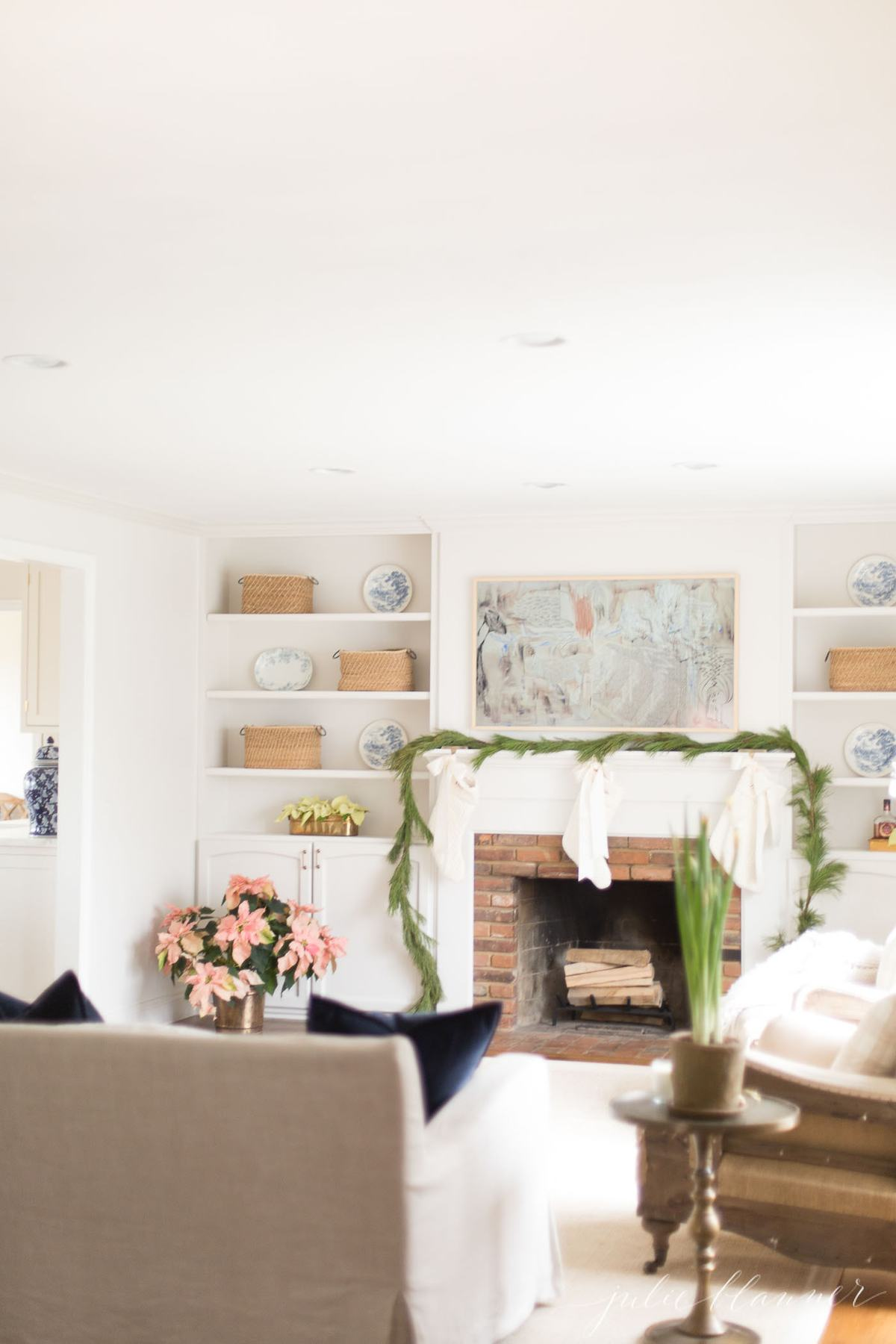 A white living room with fresh christmas greenery on the mantel.