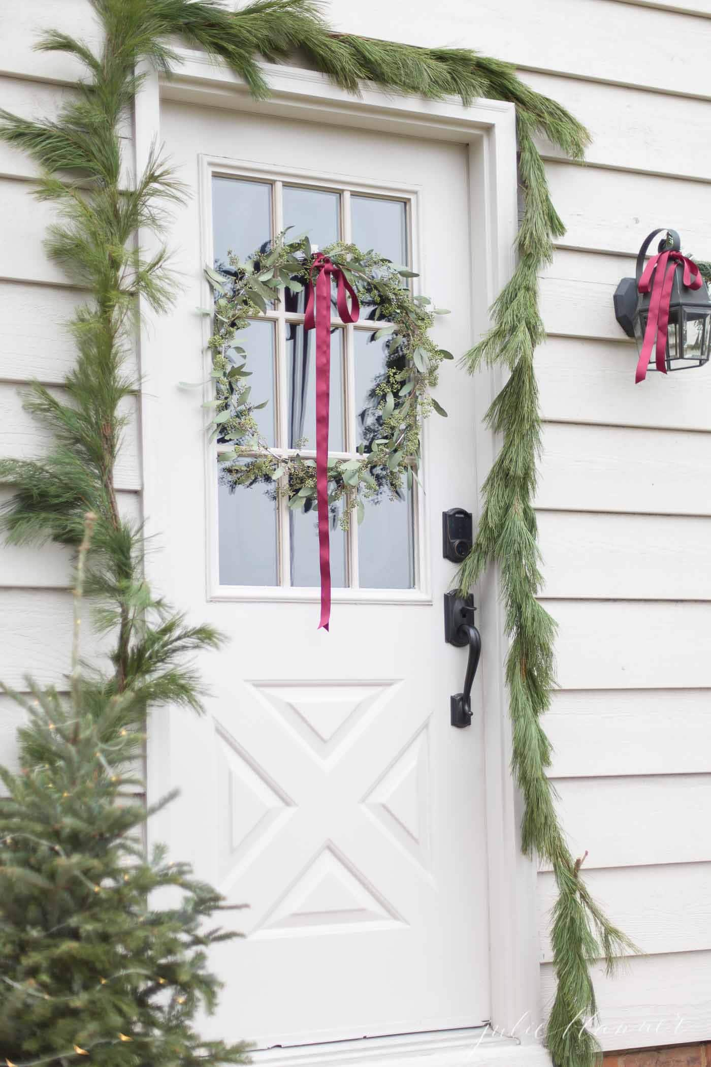 A white exterior door with a christmas wreath with a garland hanging around it.