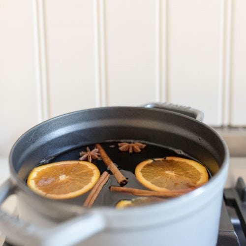 non alcoholic mulled wine recipe in a gray dutch oven on the stovetop