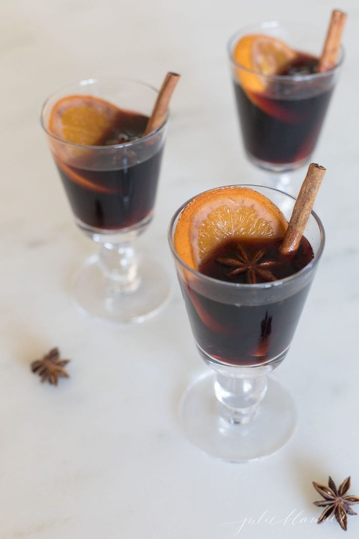 three glasses of non alocholic mulled wine with orange slice, star anise, cinnamon stick