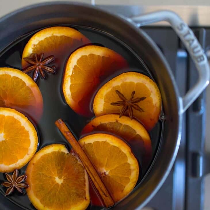 mulled wine with mulling spices and oranges in cast iron on stove
