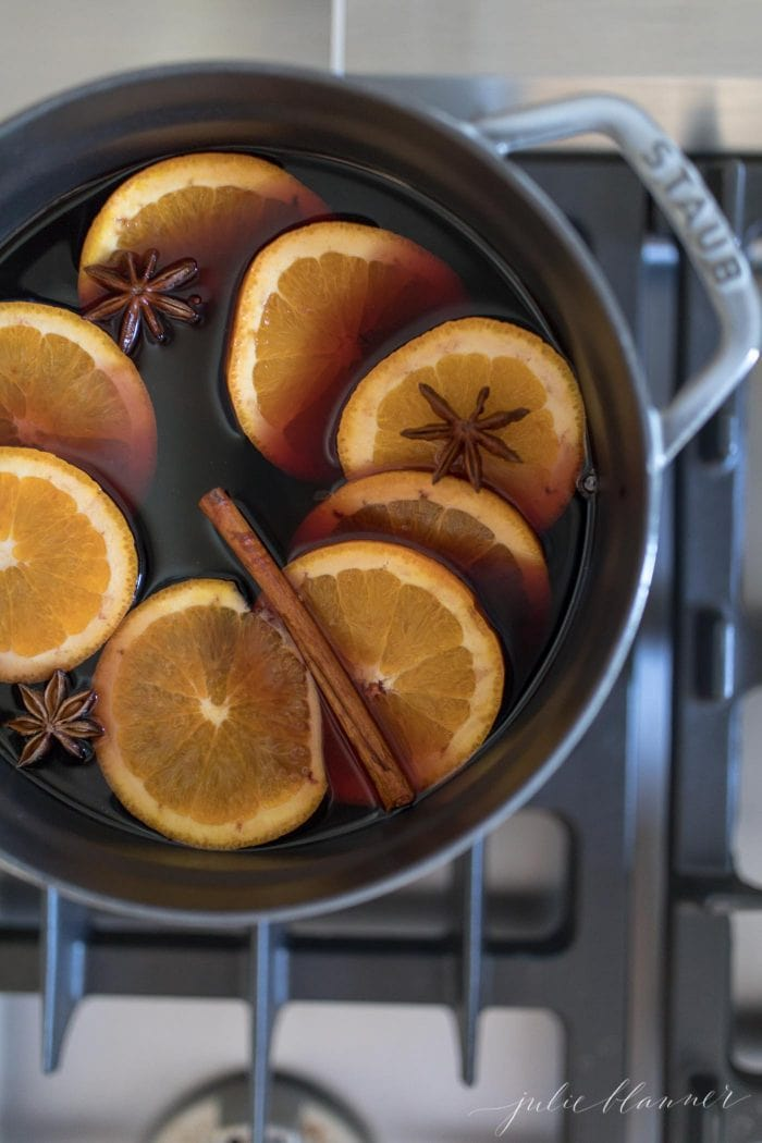 non alcoholic mulled grape juice on the stovetop with orange slices and spices