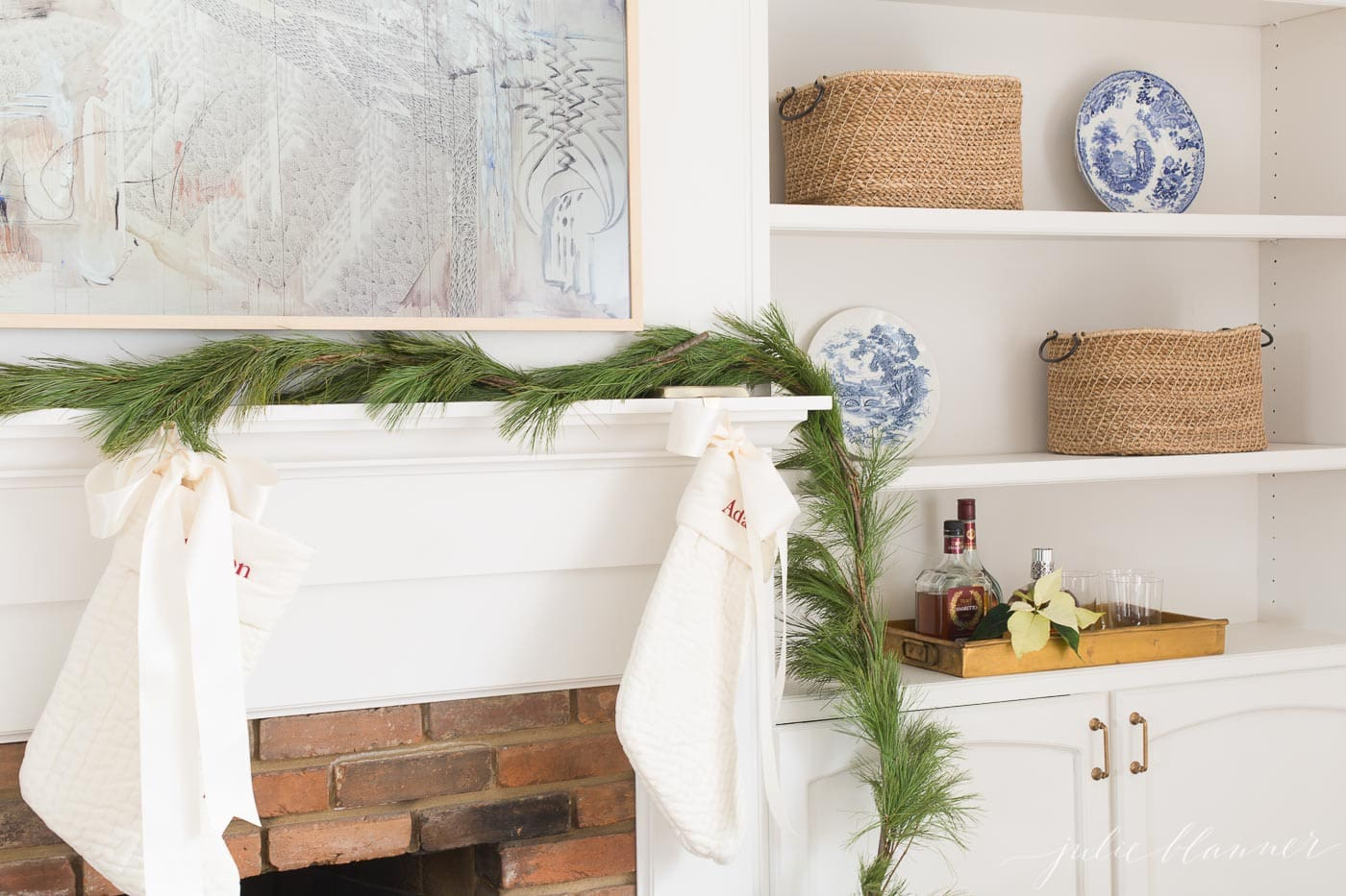 A white living room with a fresh christmas garland on the fireplace