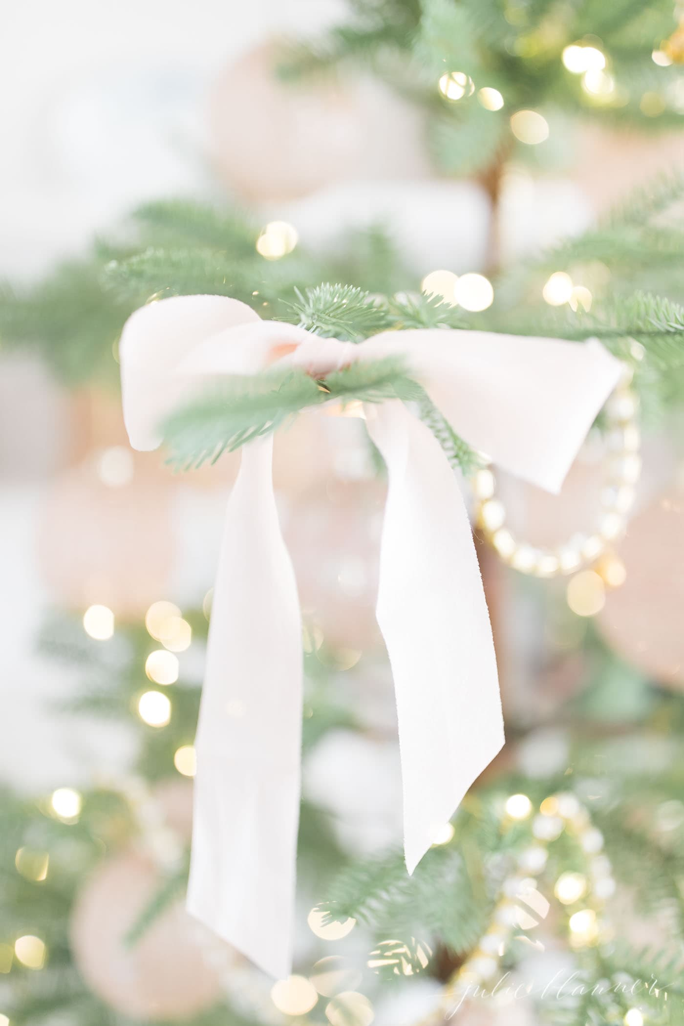 a sparse christmas tree tied with soft pink silk bows