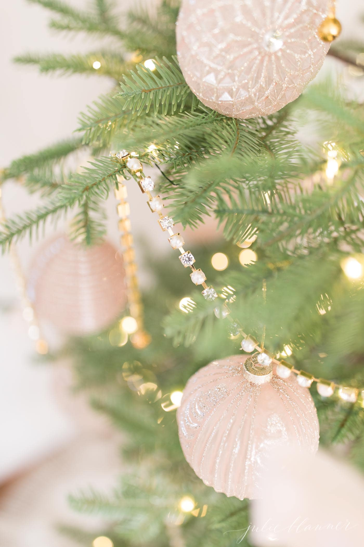 a sparse christmas tree with pink and gold ornaments