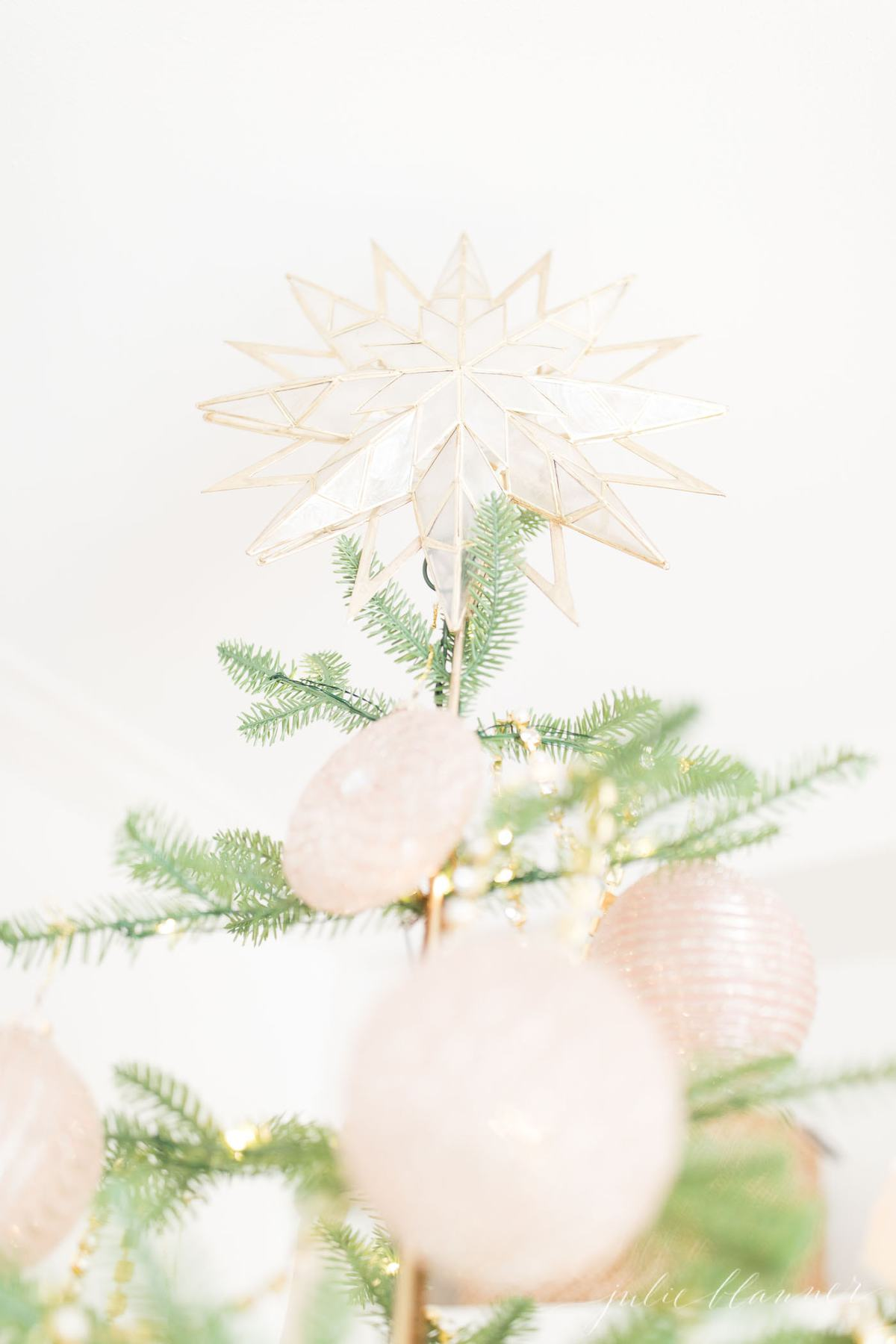 sparse christmas tree with pink ornaments and gold garlands