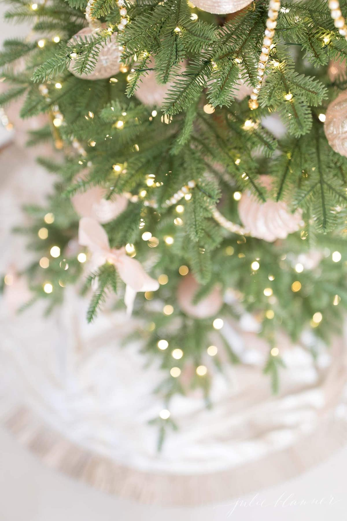 A sparse artificial christmas tree decorated in pink.