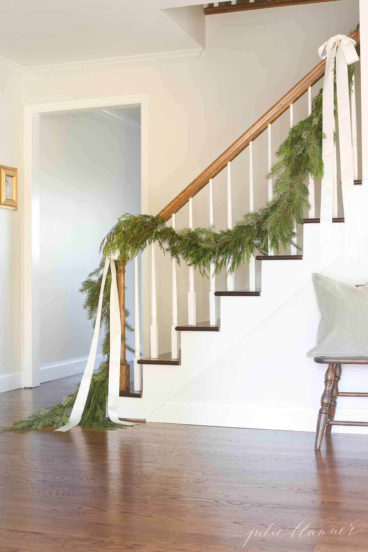 traditional stair garland tied on with ribbons in a white entryway