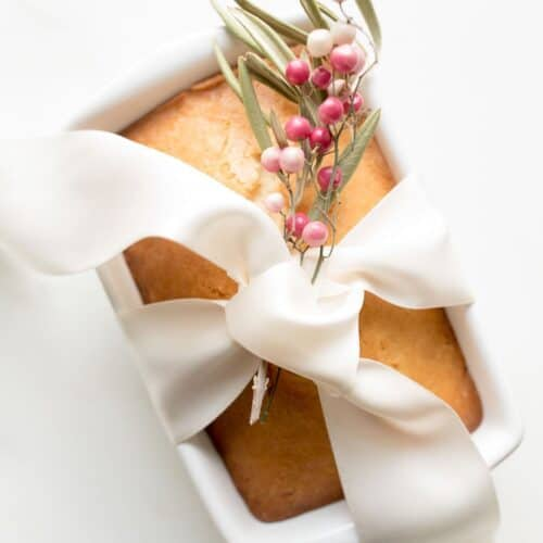 almond bread in loaf pan wrapped in ribbon with berries to gift