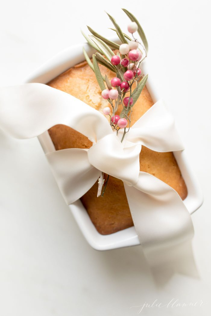 almond bread in white loaf pan with ivory ribbon and garnished with berries for gifting