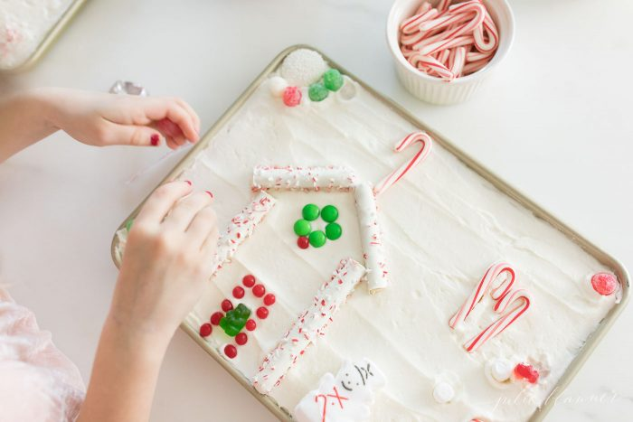 girl decorating christmas cookie sugar cookie cake gingerbread house