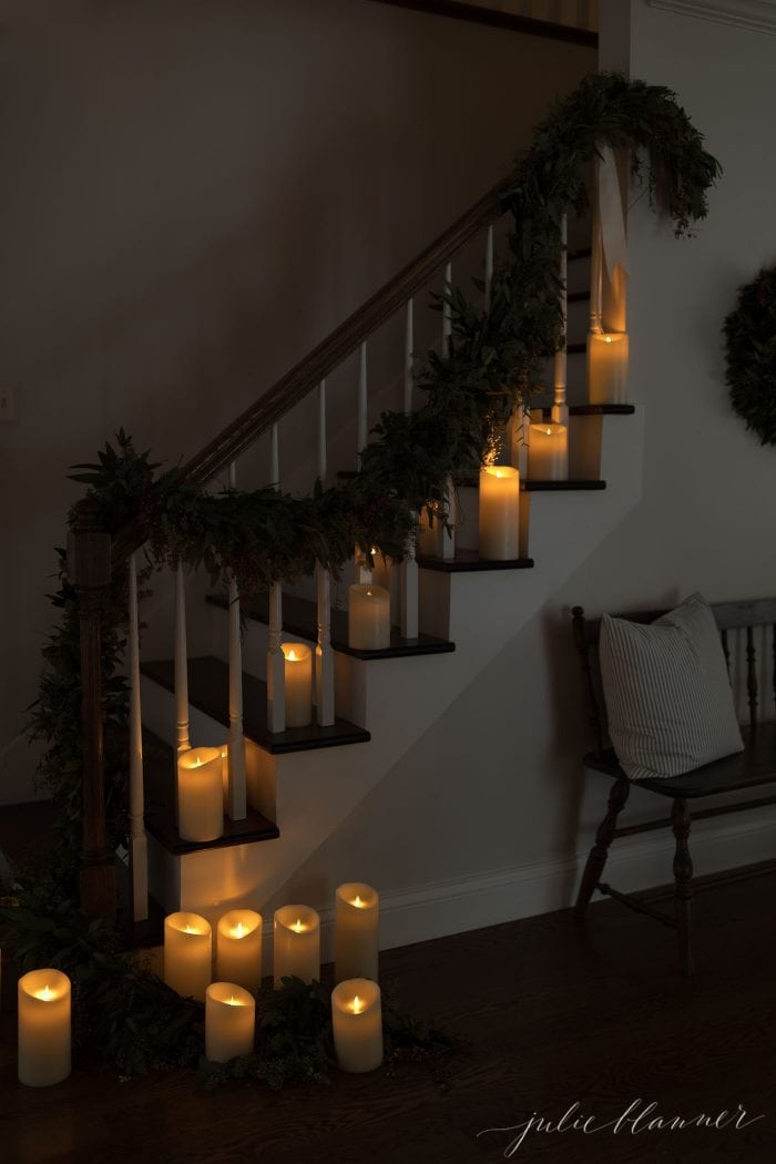 Stairs lined with candles and festive greenery.