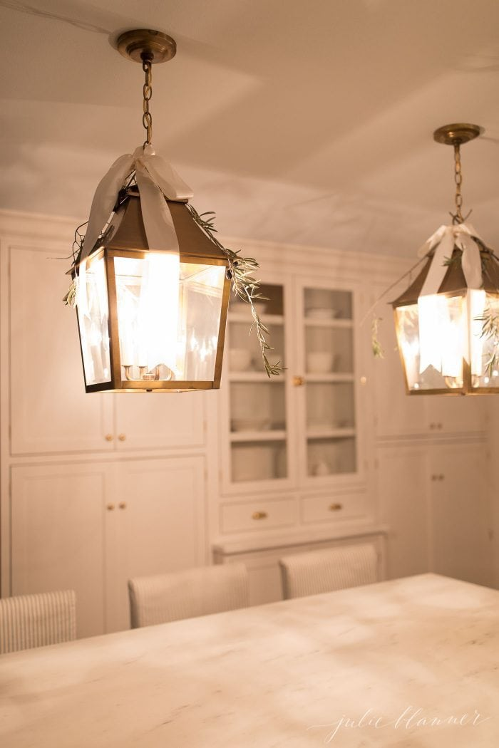 2 hanging brass lanterns with greenery and ribbons